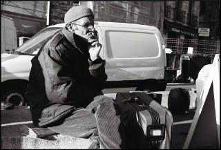 Un vieil Arabe attend, assis sur ses valises.