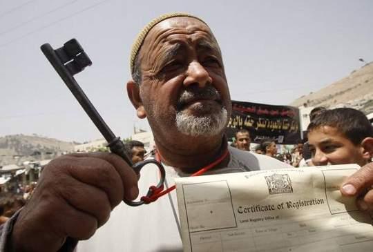 Un Palestinien manifeste en brandissant la clé et l'acte de propriété de sa maison dépossédée.