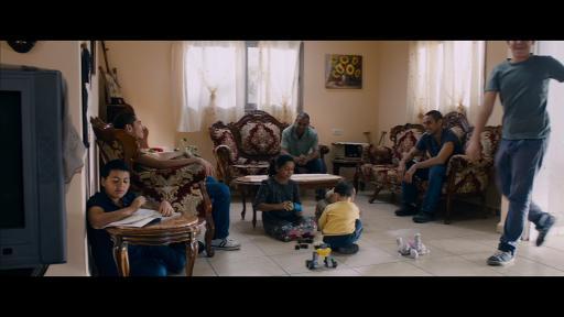 Amjad, Tarek et Omar sont assis dans le salon. Des enfants jouent à leurs pieds.