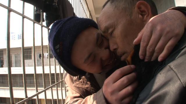Un prisonnier joyeux enlace un prisonnier triste.