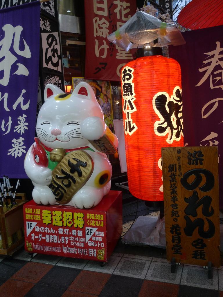 Un chat porte-bonheur qui sourit, avec sa patte articulée levée.