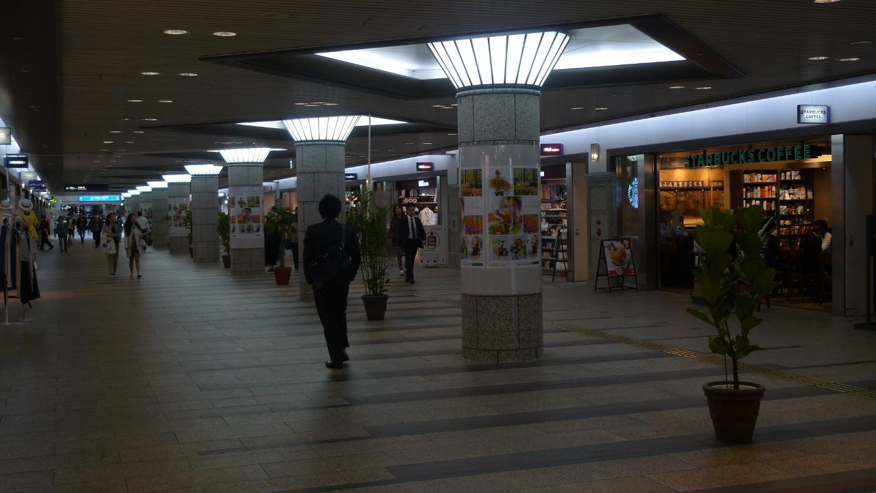 Des hommes en costume traversent une longue voie illuminée bordée de magasins.