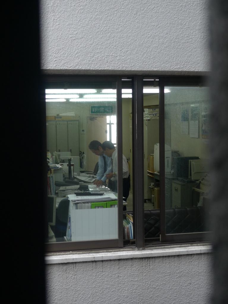 Deux hommes d'âge mûr en costume-cravate, dans un bureau encombré d'ordinateurs et de documents.