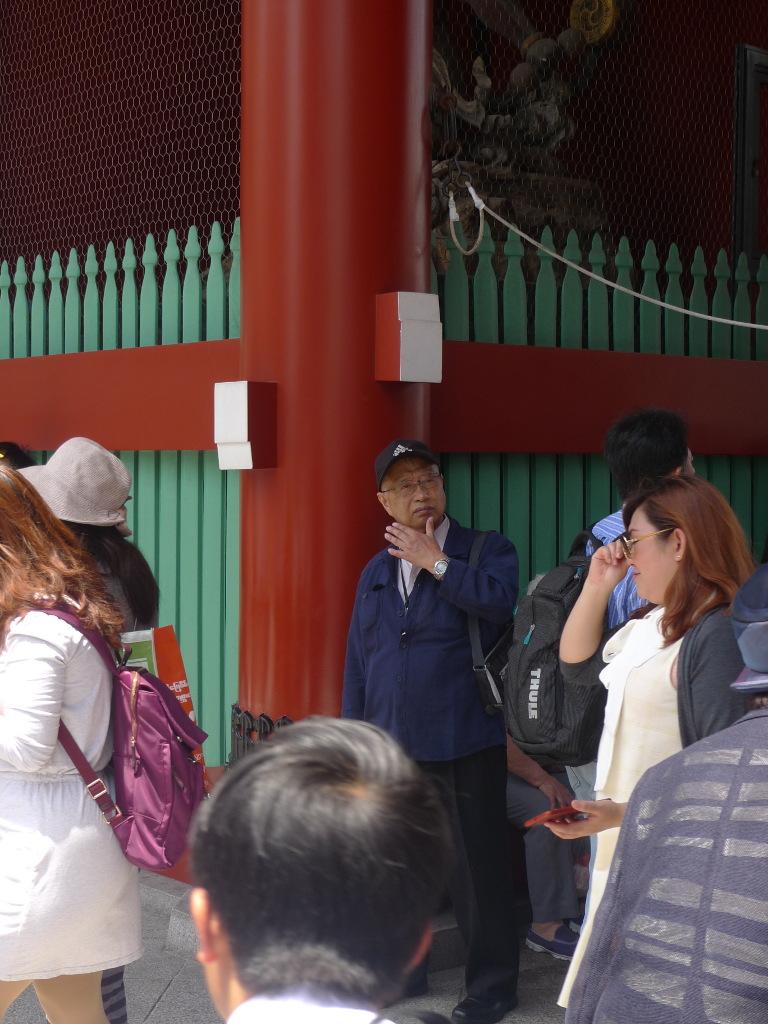 Un vieil homme, appuyé contre une colonne, regarde vers le haut, au milieu d'une foule sans visage.