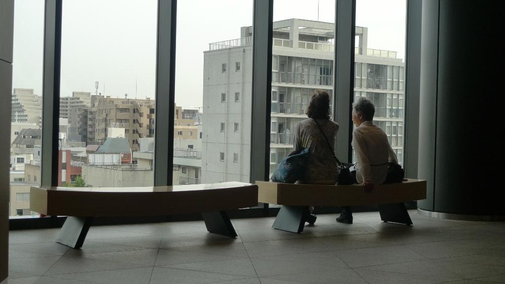 Deux femmes assises regardent une ville derrière une baie vitrée.