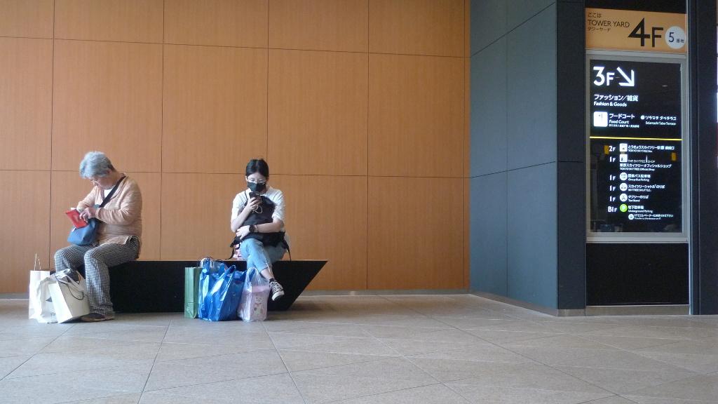 À gauche, une vieille fouille son portemonnaie. À droite, une jeune consulte son téléphone.